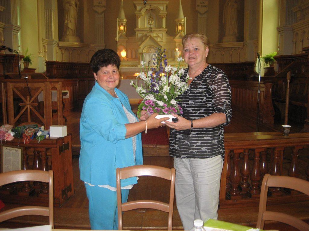Louise remet des fleurs à Huguette en reconnaissance des années consacrées à l'Association. Sainte-Marie de Beauce, août 2015. Photo de Nicole Drapeau